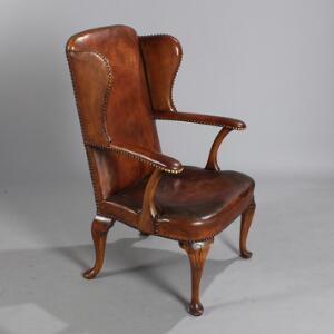 Øreklapstol med stel af egetræ, på let svungne ben med pad-feet. Queen Anne form. Udført hos Lyberg  Hansen. 20. årh.s begyndelse.