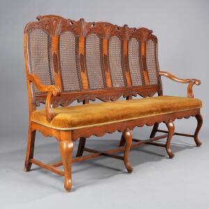 Fritstående tre-personers canapé af nød og elm, på let svungne ben, ryg med rørflet og intarsia. Rococo-form. 19. årh. H. 119. L. 194. D. 55.