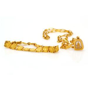Smykkesæt af 21,6 kt. guld bestående af armbånd og kæde med vedhæng i form af formentlig forgyldt Buddha indkapslet i kunstmateriale. L. ca. 17,5 , 44 og 1,7 cm