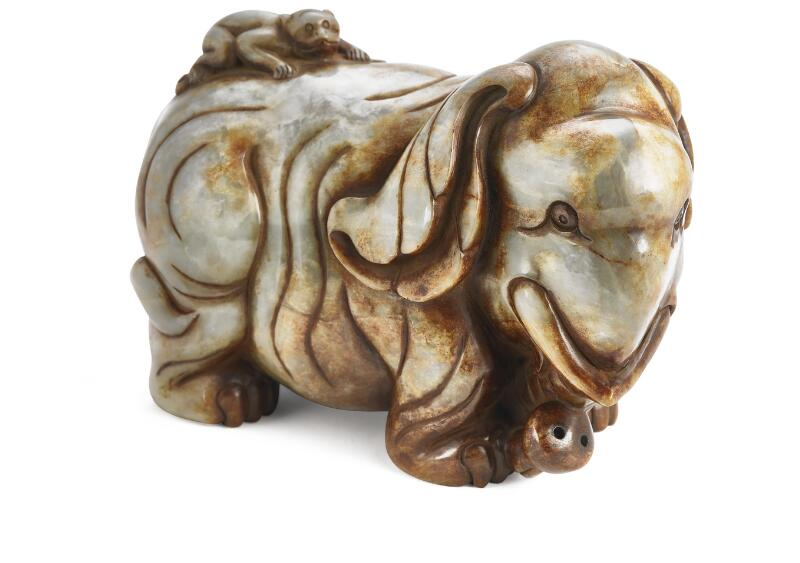 A Chinese figurine of greyish brown jade in the shape of an elephant with a...