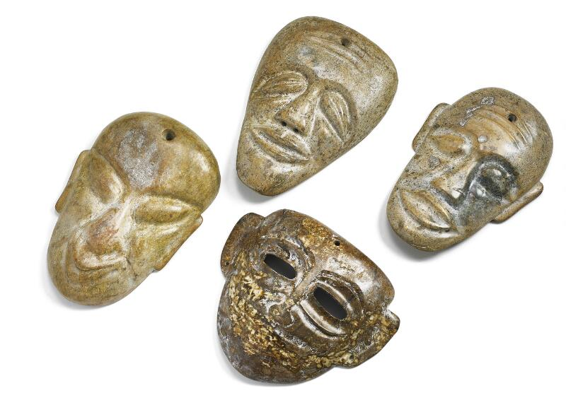 Four Chinese masks of brownish jade. Weight 3954 g. H. 18–23 cm. (4)