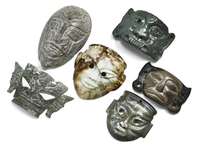 Six Chinese masks of brown and greenish jade, one with coloured eye inlay...