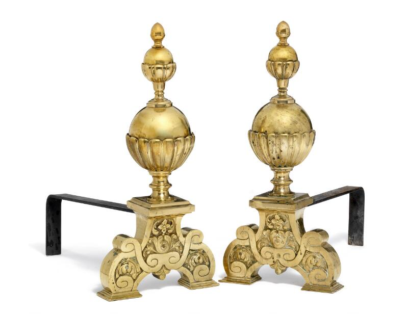 A large pair of Baroque style brass fire dogs, with ball finals and scroll...