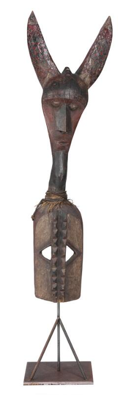 Large helmet mask of carved patinated wood with traces of black and red...
