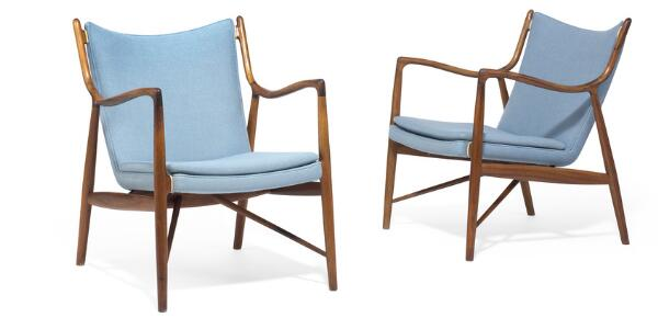 """Finn Juhl: """"FJ 45"""". A pair of easy chairs of Brazilian rosewood. Seat, back and loose cushion upholstered with light blue wool, edgings of natural leather. (2)"""